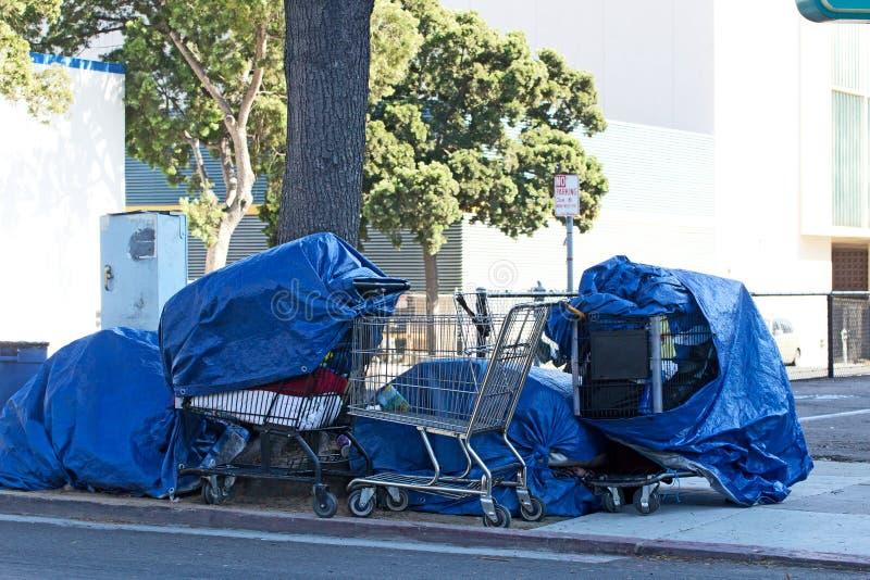 Affaires sans foyer de Peopleâs dans des chariots d'épicerie photos stock