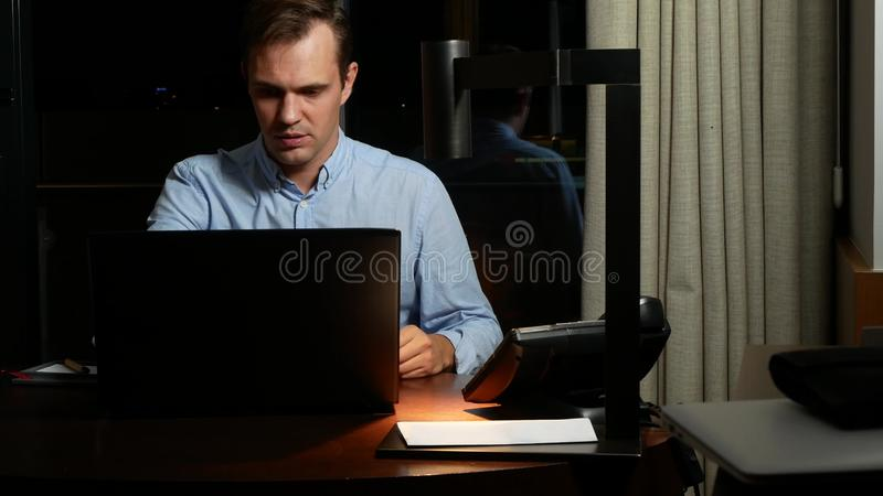 Affaires, surmenage, date-butoir et concept des personnes - un homme travaillant sur un ordinateur portable la nuit image libre de droits
