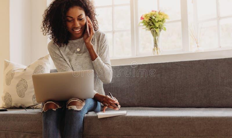 Affare in carico dell'imprenditore della donna dalla casa con il telefono cellulare fotografia stock libera da diritti