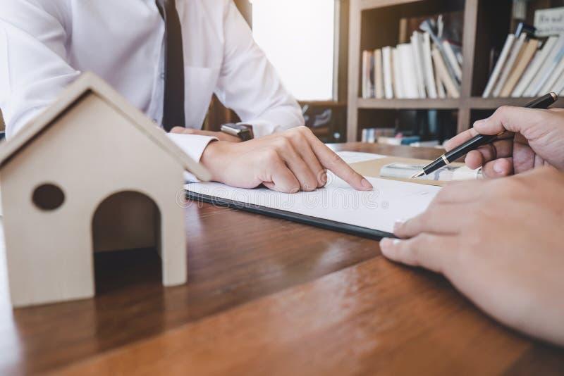 Affare che firma una casa compra-vendita del contratto, segno dell'uomo una casa dentro immagini stock