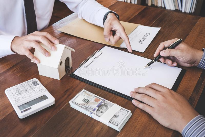 Affare che firma una casa compra-vendita del contratto, segno dell'uomo una casa dentro fotografia stock