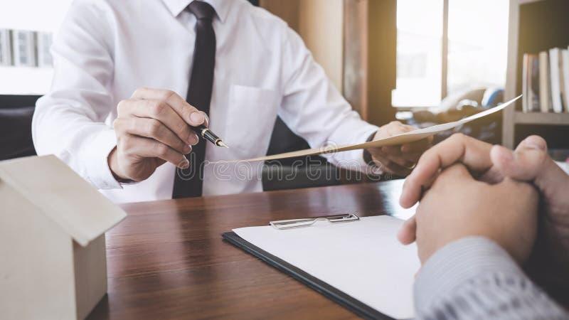 Affare che firma una casa compra-vendita del contratto, segno dell'uomo una polizza d'assicurazione domestica sui prestiti immobi immagine stock