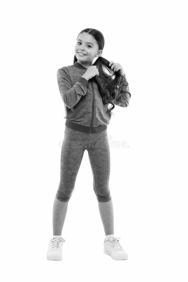 Affare con capelli lunghi mentre esercitandosi Risolvendo con i capelli lunghi Il bambino sveglio della ragazza con le code di ca fotografia stock libera da diritti