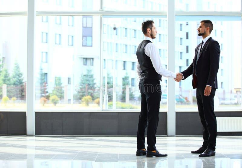 Affare e concetto dell'ufficio - due uomini d'affari che stringono le mani fotografia stock libera da diritti