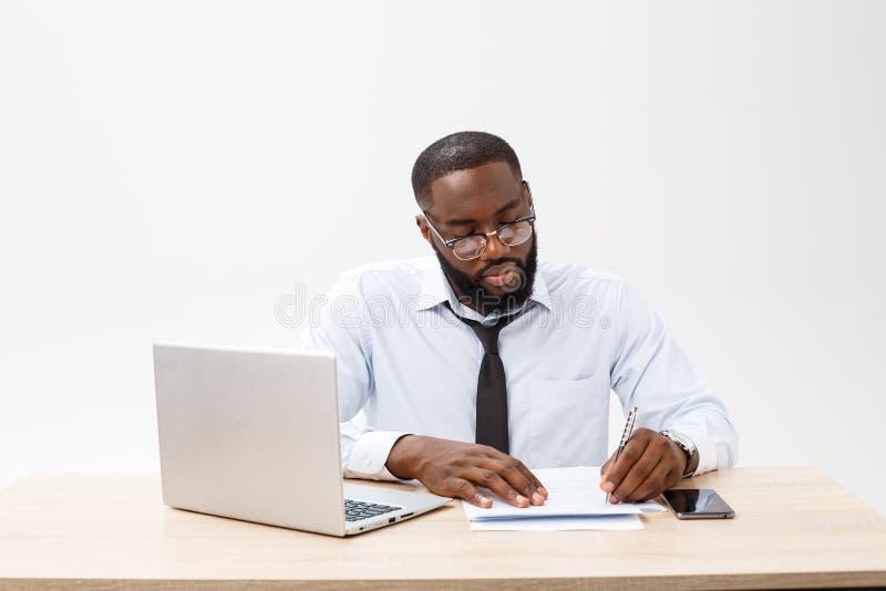 Affare e successo Riuscito uomo afroamericano bello che indossa vestito convenzionale, facendo uso del computer portatile per dis immagine stock libera da diritti