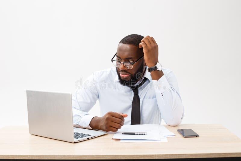 Affare e successo Riuscito uomo afroamericano bello che indossa vestito convenzionale, facendo uso del computer portatile per dis fotografie stock libere da diritti