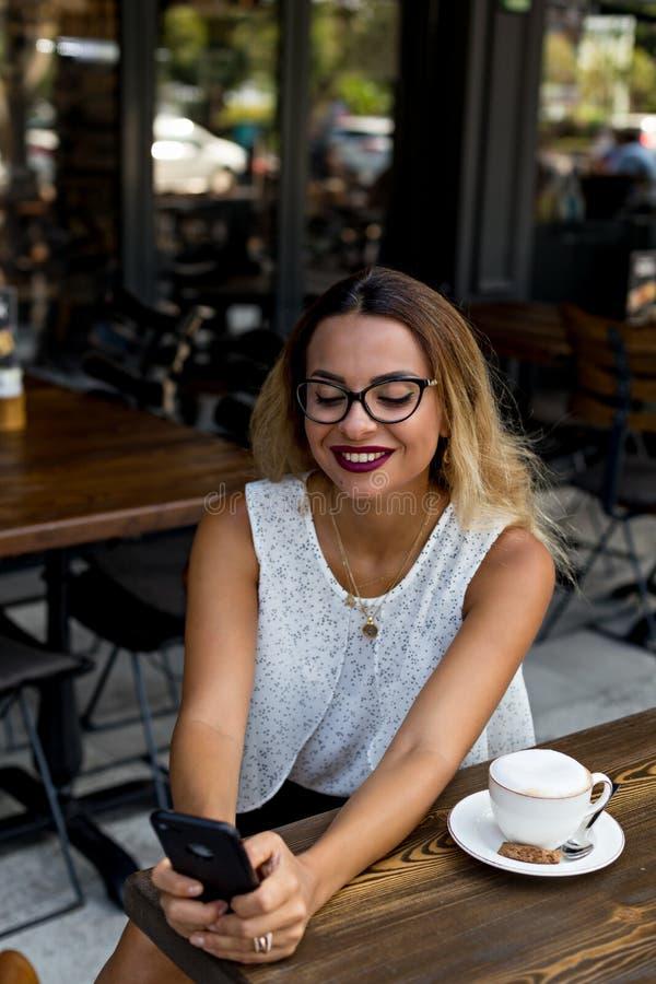 Affare elegante femminile in un caffè all'aperto con il telefono cellulare immagine stock