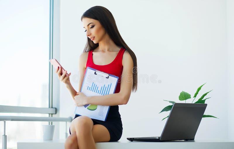 Affare Giovane donna di affari che si siede sulla Tabella nel grande ufficio leggero Ragazza vestita in maglietta rossa e gonna n immagine stock