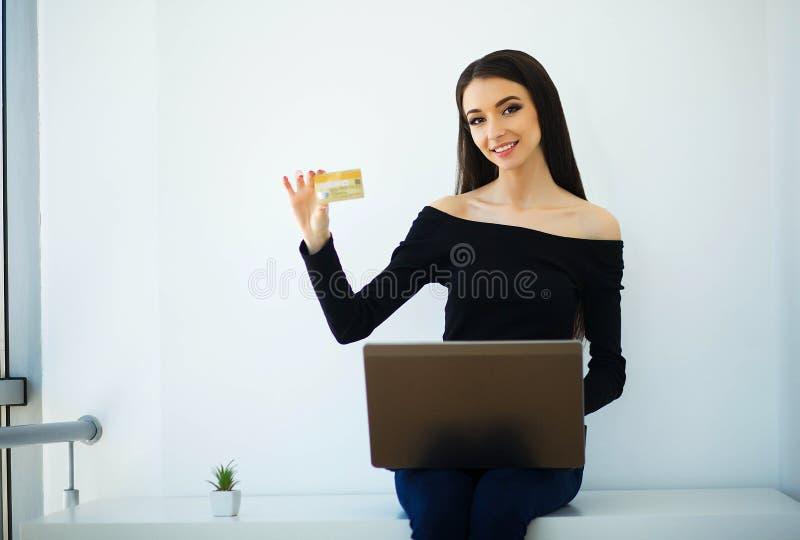 Affare Giovane donna di affari che tiene la carta di credito in mani Si siede sulla Tabella al grande ufficio leggero e sugli imp fotografie stock