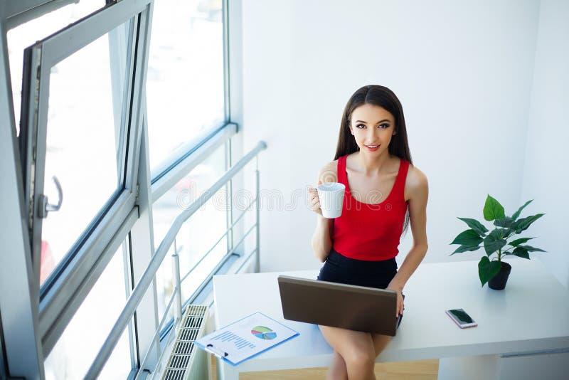 Affare La bella giovane donna vestita in maglietta rossa e gonna nera sta lavorando al computer Tazza in mani Ragazza fotografia stock libera da diritti