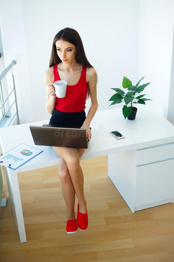 Affare La bella giovane donna vestita in maglietta rossa e gonna nera sta lavorando al computer Tazza in mani Ragazza fotografia stock