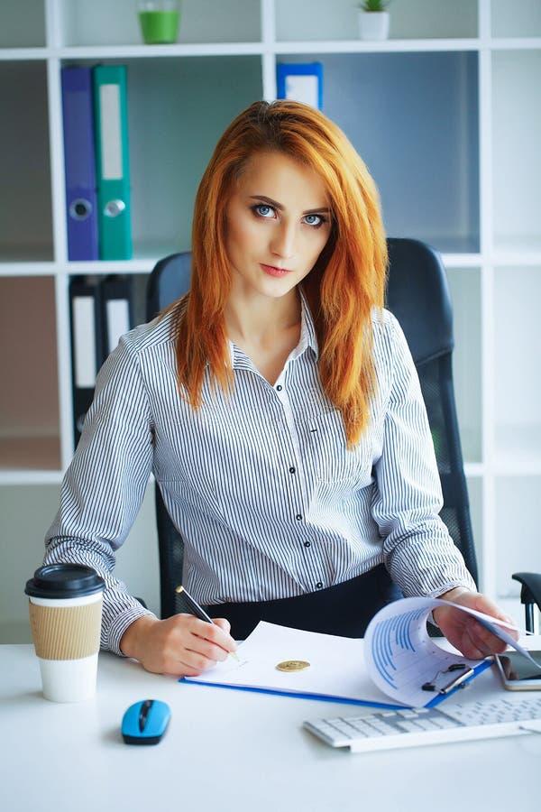 Affare La donna di affari con capelli rossi si siede allo scrittorio alla B fotografie stock libere da diritti