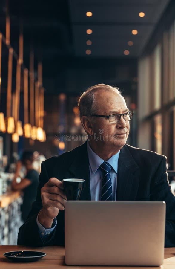 Affare senior alla tavola del caffè con il caffè bevente del computer portatile immagini stock