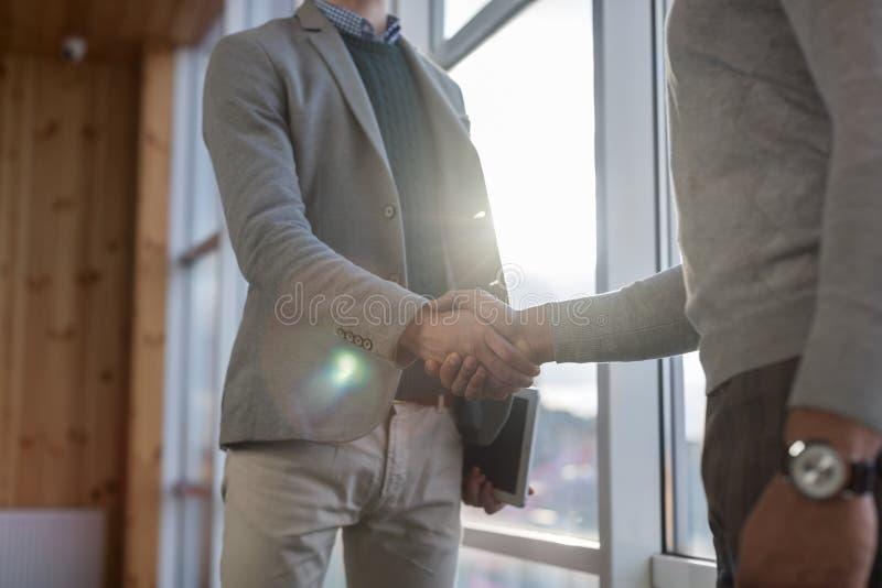 Affare Team Coworkers Stand del centro di Coworking di accordo della mano di scossa dell'uomo di affari due in grande finestra pa fotografie stock