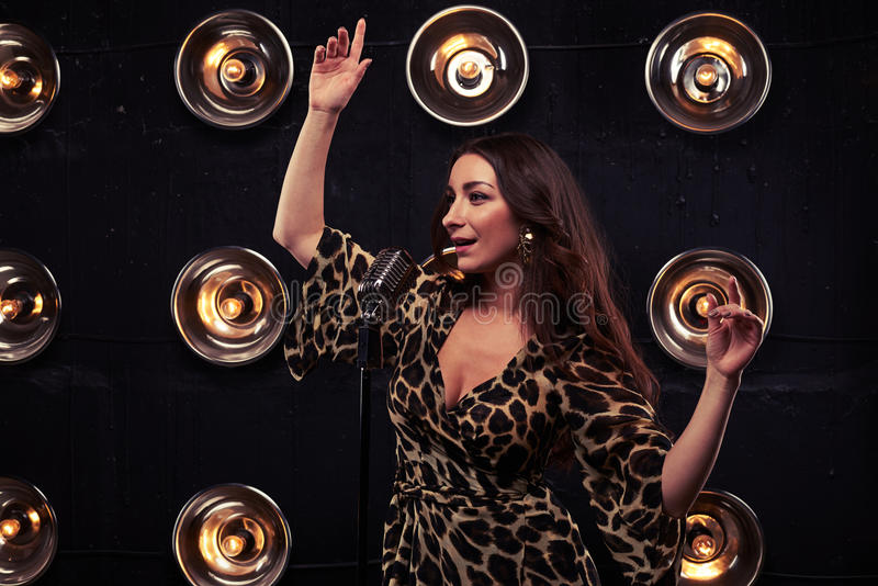 Affecting brunette in a leopard dress with hands up looking royalty free stock image