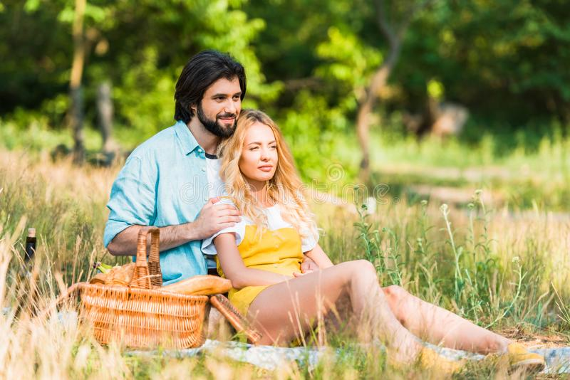affectionate couple hugging and sitting on grass royalty free stock photos