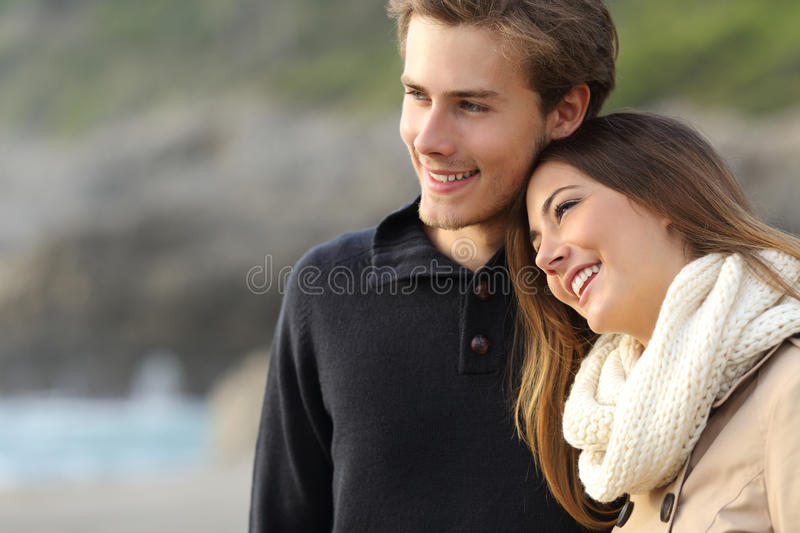 Affectionate couple looking away on the beach stock photography