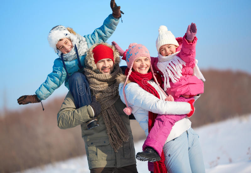 Affectionate family. Happy parents holding kids in winterwear and looking at camera outside royalty free stock images