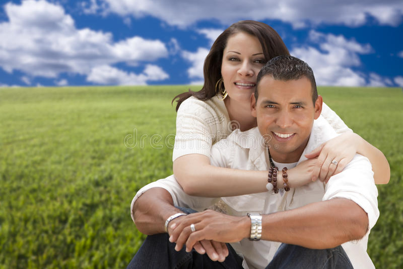 Affectionate Hispanic Couple Hugging in Grass Field stock photo