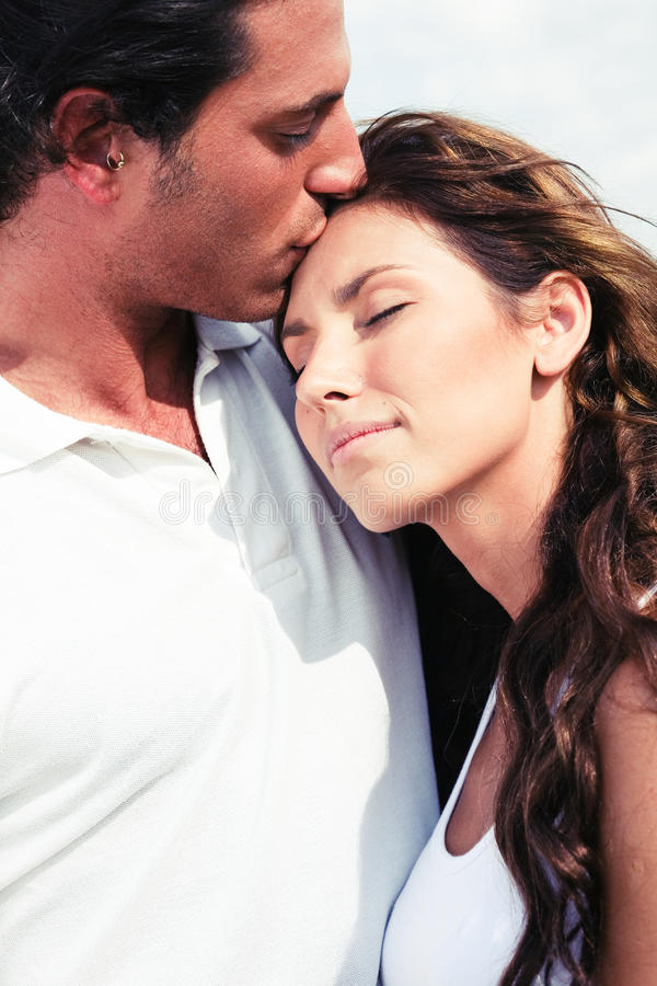Affectionate man kissing. Young man kissing on forehead stock image