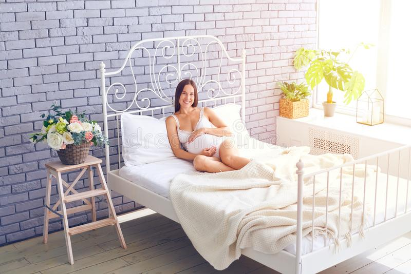Affectionate pregnant woman relaxing in the bedroom royalty free stock photography