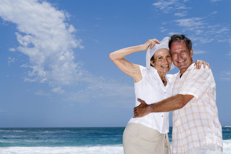 Affectionate senior couple embracing on beach, woman holding sun hat, smiling, portrait stock image