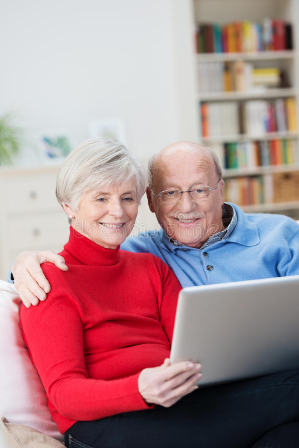 Affectionate senior couple sharing a tablet-pc stock images