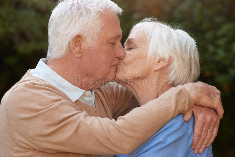 Affectionate seniors in love hugging and kissing outdoors royalty free stock image