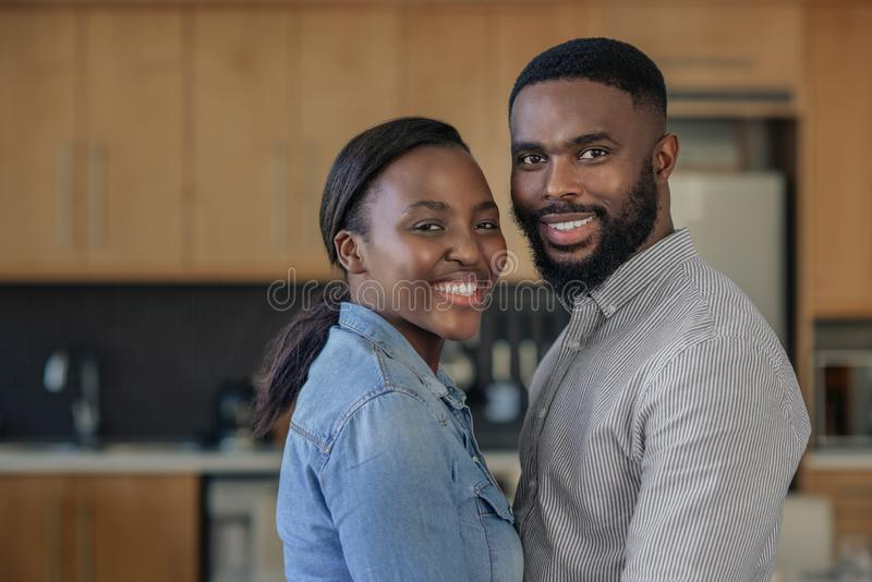 Affectionate young African American couple standing close together at home. Portrait of an affectionate young African American couple smiling while standing stock photography