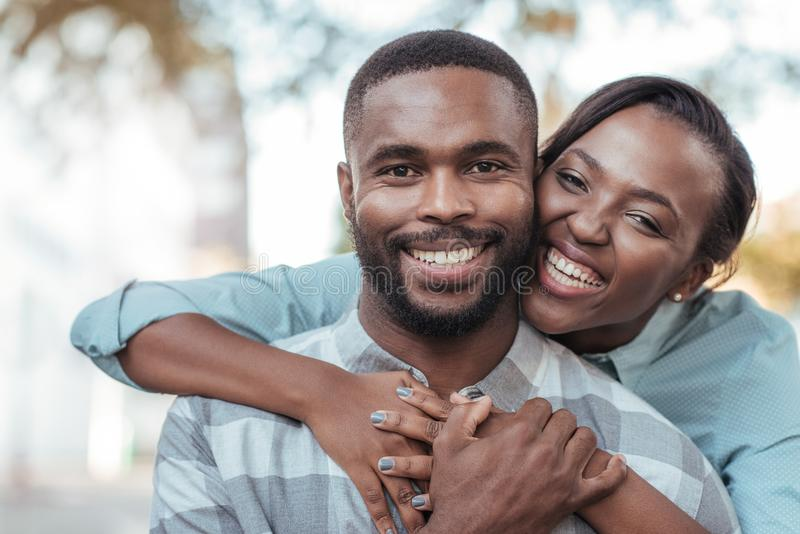 Affectionate young African couple standing outside on a sunny day stock photos