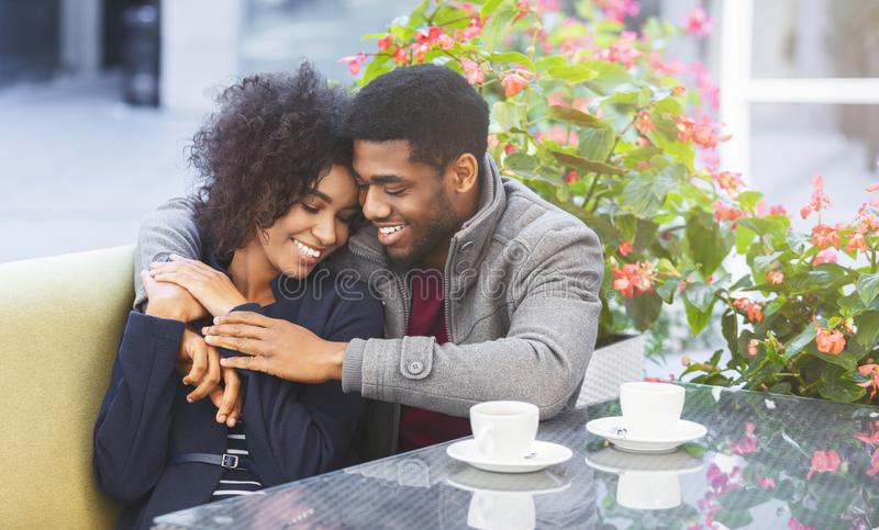 Affectionate young couple cuddling in cafe during date royalty free stock photo