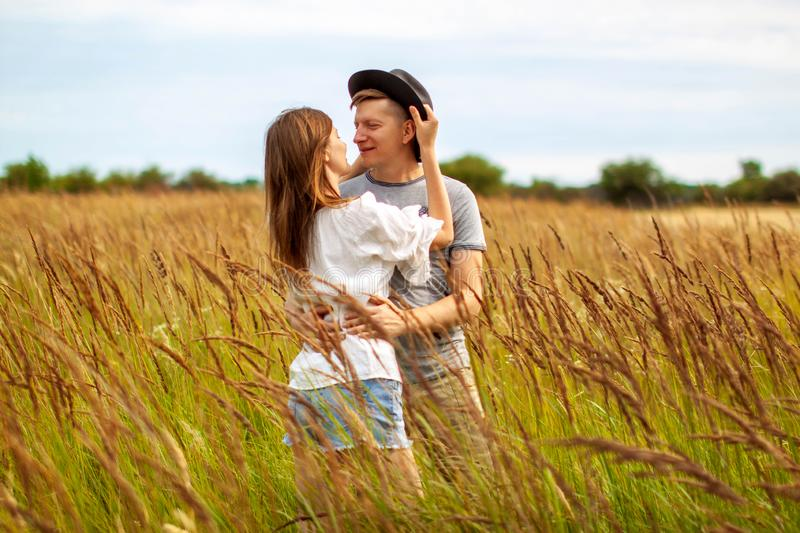 Affectionate young couple hugging in sunny rural field. royalty free stock photo