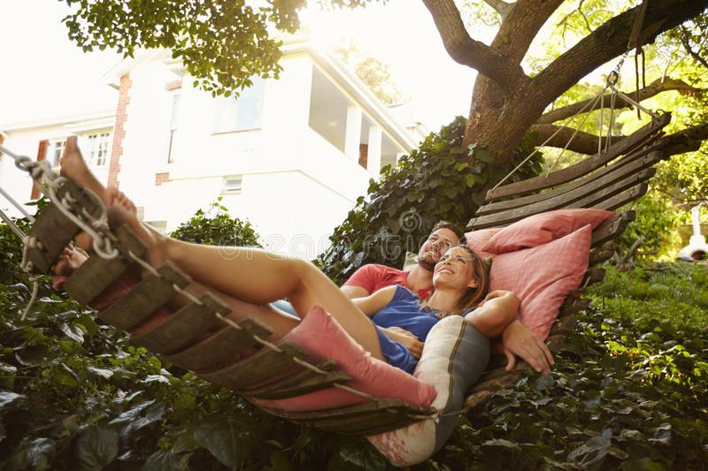 Affectionate young couple lying on garden hammock. Portrait of an affectionate young couple lying on a hammock looking away smiling. Romantic young men and women royalty free stock photo