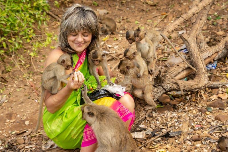 Affen umgaben einen glücklichen Touristen, der sie mit Frucht einzieht lizenzfreies stockbild
