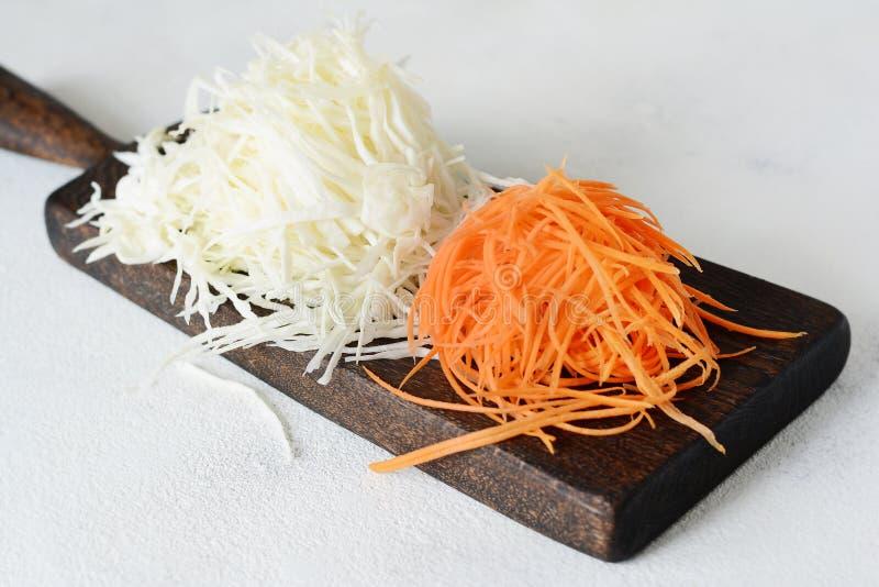 Affettare cavolo e le carote freschi su un bordo di legno su un fondo leggero Verdure per fermento, per fermentazione lunga fotografie stock