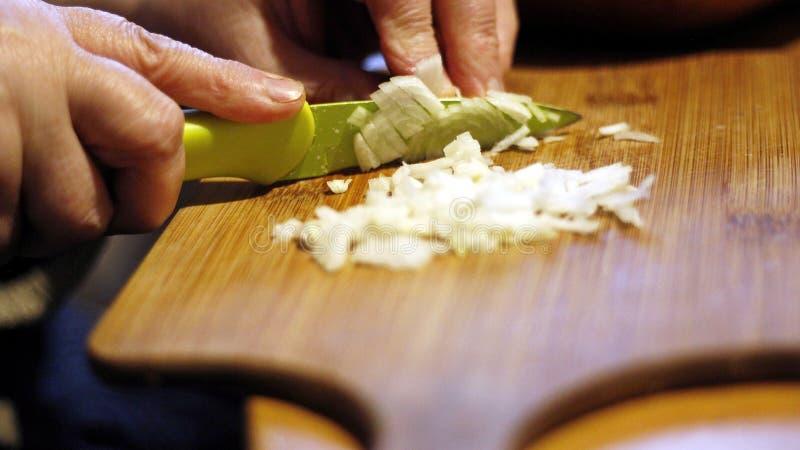 Affettare le cipolle nella cucina fotografie stock libere da diritti