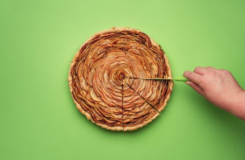 Affettare torta di mele su un fondo di Libro Verde immagine stock