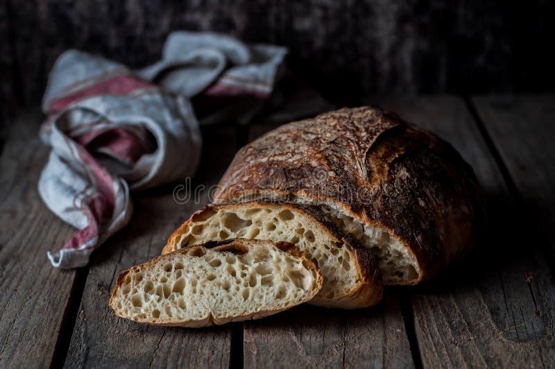 Affettato intorno al nessun impasti il pane rustico su una superficie di legno fotografia stock