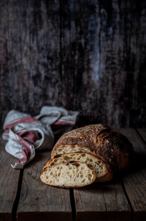 Affettato intorno al nessun impasti il pane rustico su una Tabella di legno fotografie stock