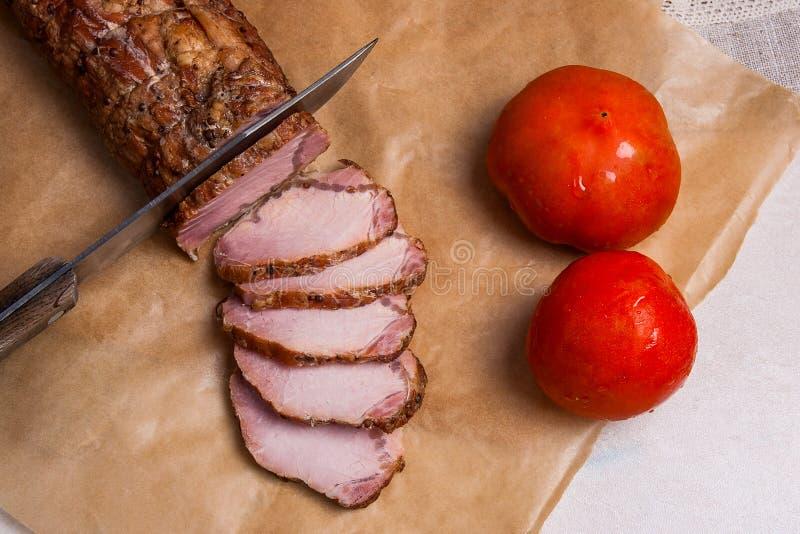 Affetti la carne o prosciutto affumicato, coltello e due pomodori su packin marrone immagine stock libera da diritti