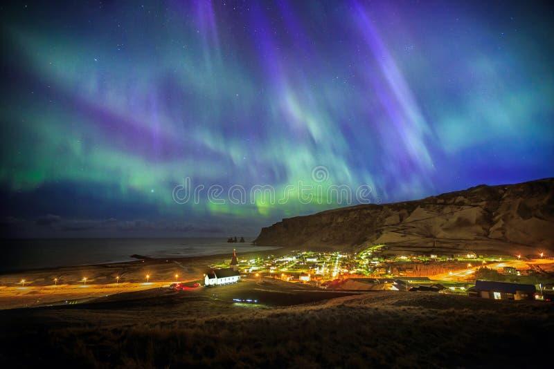 Affichage auroral au-dessus de ville de Vik photographie stock libre de droits