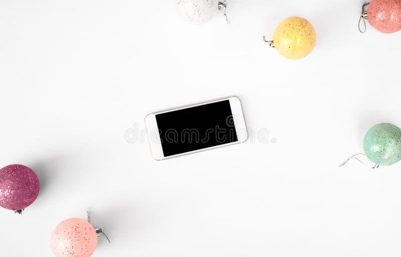 Affichage mobile de téléphone intelligent sur le fond de composition en Noël de table wallpaper, les cônes de pin, boules de déco photo stock