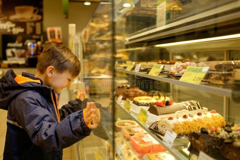 Affichage proche de petit garçon avec des gâteaux image libre de droits