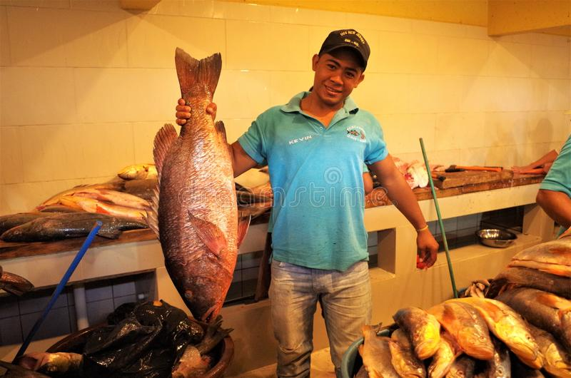 Affichage traditionnel de marché de fruits de mer chez l'homme de Tegucigalpa Honduras tenant un grand poisson à vendre photographie stock