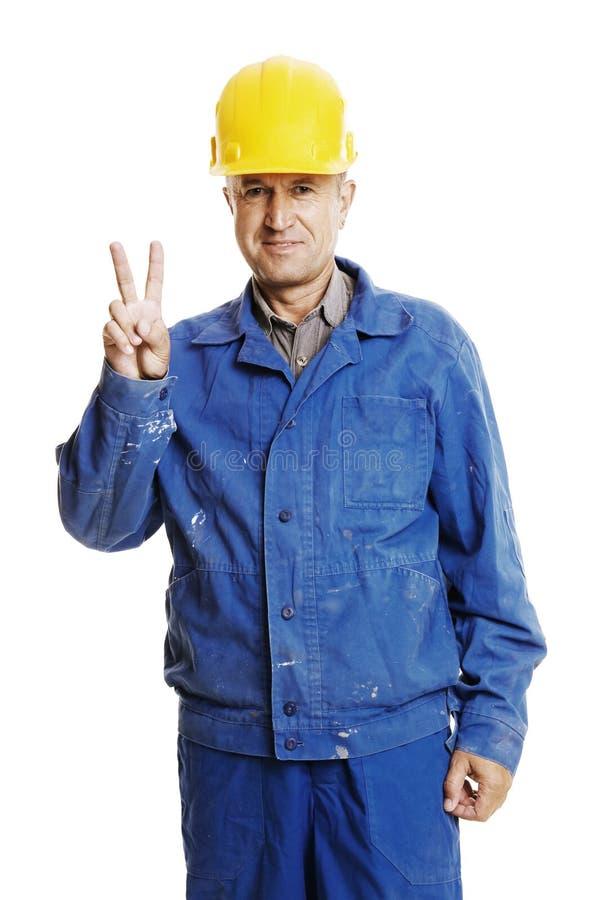 affichant à signe l'ouvrier souriant de victoire photo libre de droits