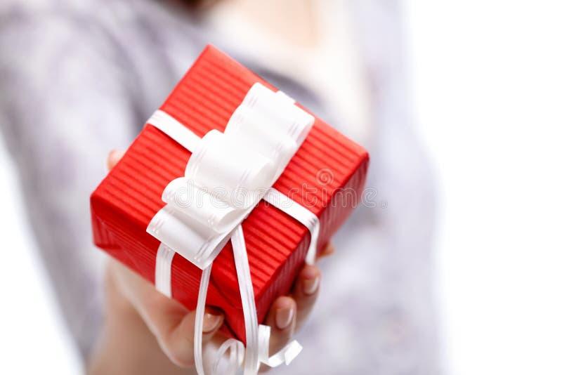 Affichant le présent enveloppé en papier rouge de cadeau image stock