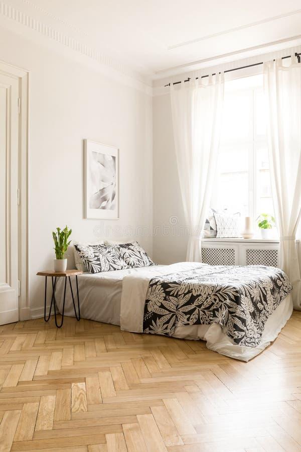 Affiche au-dessus de lit avec la couverture modelée dans la chambre à coucher blanche i d'hôtel photographie stock