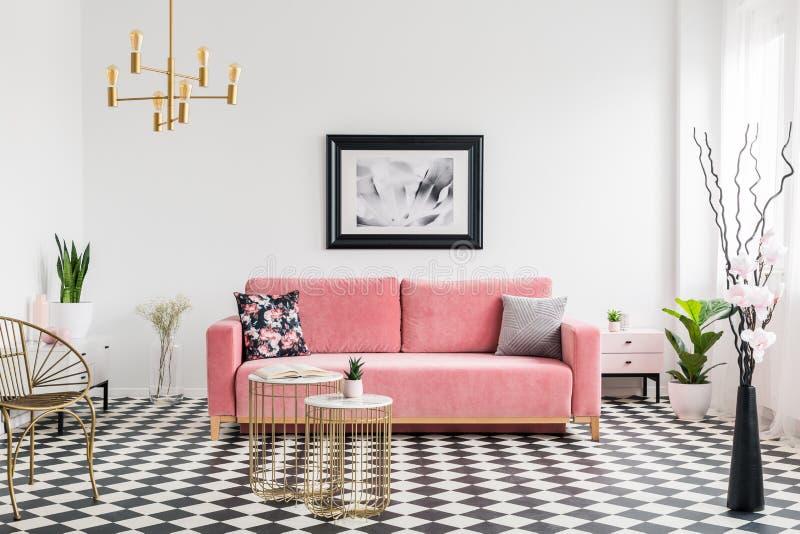 Affiche boven roze sofa in ruim woonkamerbinnenland met installaties en gouden leunstoel Echte foto stock fotografie