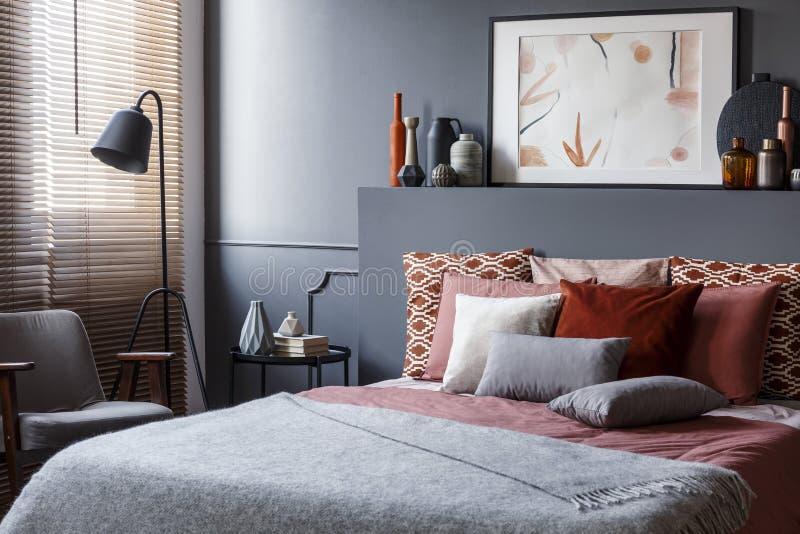Affiche créative sur la tête de lit noire au-dessus du lit confortable avec décoratif photographie stock libre de droits