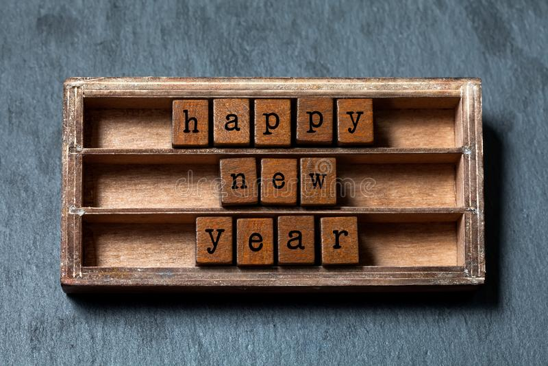 Affiche d'invitation de carte de voeux de bonne année Boîte de vintage, cubes en bois avec des lettres de style ancien Pierre gri photo libre de droits